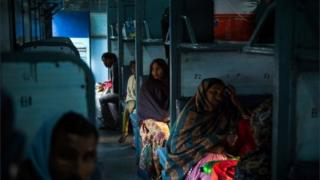 An Indian woman sits inside a carriage as she waits for a train to leave Hazrat Nizamuddin railway station in New Delhi on February 25,2016