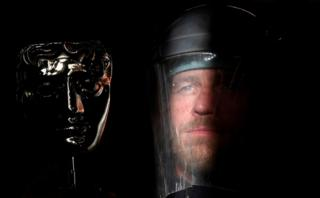 Ray Terry, a furnace man at the foundry where the castings of the iconic British Academy of Film and Television Awards (BAFTA) masks are made, poses with a finished mask, ahead of the annual awards ceremony, London.