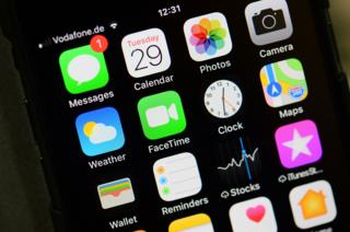 An iPhone home screen is pictured showing its many apps