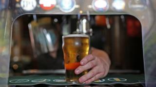 Man serves pint from behind plastic screen
