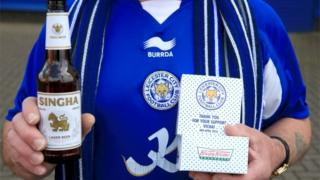 Leicester City fan holds his free beer and doughnut before the Premier League match against Southampton at the King Power Stadium