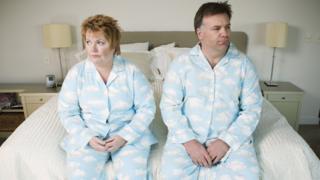 Hombre y mujer vestidos iguales y sentados en el borde de la cama con cara de descontento.