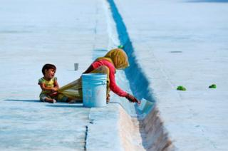 A woman paints the floor of a pond as her child pulls at her sari in Delhi, India