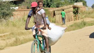 A man with a child o his back cycling in Epworth, Zimbabwe - Tuesday 31 March 202