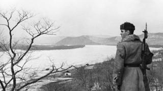 Советский пограничник на правом берегу Уссури. Напротив - остров Даманский (1969 год)