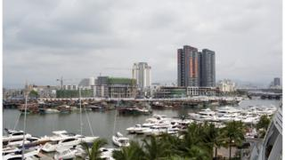 Luxury yachts sit docked at the Visun Royal Yacht Club in front of fishing boats and residential developments in the Sanya Bay district of Sanya, Hainan Province, China, on Monday, April 7, 2014.