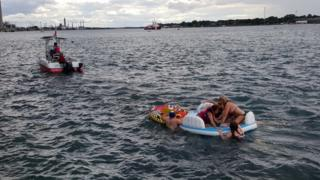 A Canadian Coast Guard ship tows floatation devices used by U.S. partiers