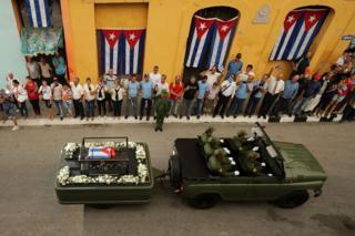 Una camioneta lleva el ataúd con los restos de Fidel Castro mientras las personas a ambos lados de la calle observan y saludan con banderas cubanas en silencio