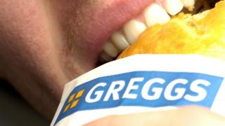 Person eating a Greggs pasty