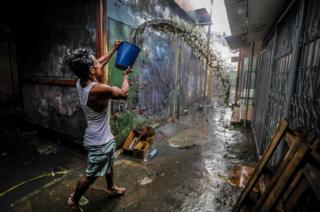 Un hombre lanza un balde de agua a uno los locales del Mercado Oriental en Managua, Nicaragua, que a principios de esta semana se incendió./