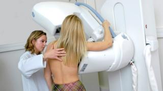 Radiographer carries out a mammogram.