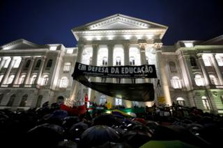 Protestors gathers outside a university filled with banners in the rain