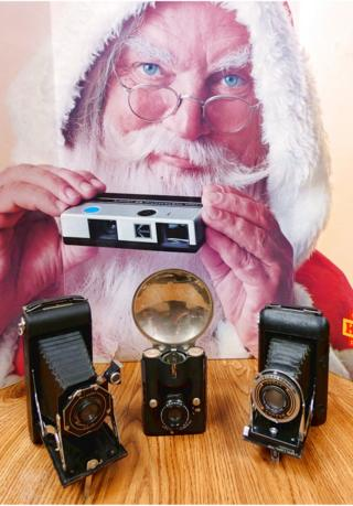 backdrop: advert for Kodak instamatic camera. Foreground, left to right: No.1 Kodal, Brownie Pliant, Six-16 folding camera (USA); Brownie Flash, Six-20, c.1941; Kodak Regent, Compur shutter, Zeiss Tessar lens, folding camera, c.1935-39 (Germany)