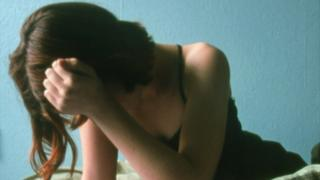 Teenage girl covering her face, file pic