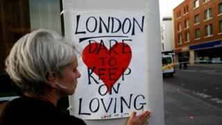 A woman attaches a sign near London Bridge in London