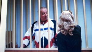 Sergei Skripal speaks to his lawyer from behind bars seen on a screen of a monitor outside a courtroom in Moscow.