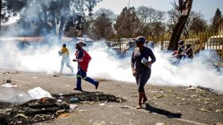 South African looters run through tear gas smoke during a riot in the Johannesburg suburb of Turffontein
