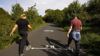 Man and woman walk on greenway