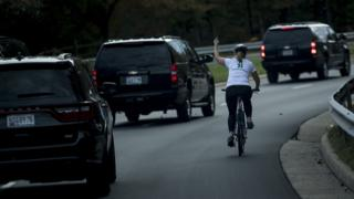 A line of motorcade cars and Juli Briskman on a cycle making a middle finger gesture