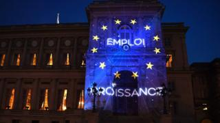 The words Employment and Growth (in French) and the logo of the European Union are projected during a light show onto the French Foreign Ministry building in Paris