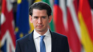Austrian Chancellor Sebastian Kurz walks in front of flags from European nations at an EU summit in March 2019