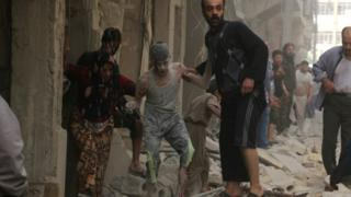 Syrians help a wounded youth following an air strike on the Fardous rebel held neighbourhood of the northern Syrian city of Aleppo