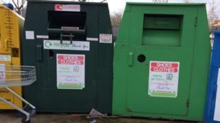 A picture of a dark green and a light green recycling bin with stickers on bearing the name: Helping Our Future.