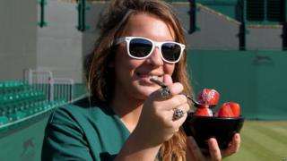 A member of ground staff at Wimbledon eats strawberries