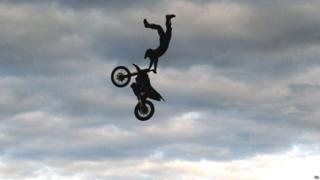 A motorcyclist from The Extreme Stunt Show takes part in a performance at Earsdon, North Tyneside, during their UK tour.