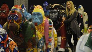 Colourful, life-size gorilla sculptures with worker from Bristol Zoo.