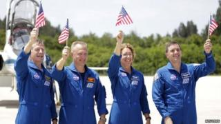 Atlantis shuttle crew waving American flags