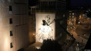 Two graffiti artists look at their painting of a mother holding a baby in Bristol.