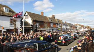A funeral cortege passes through Wootton Basset with people lining the streets