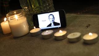 An iPhone displays an image of Steve Jobs at a makeshift memorial outside an Apple store in New York