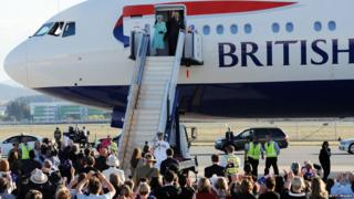Queen and Prince Philip waving on steps of plane
