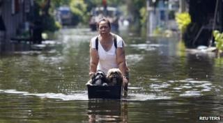 Woman pushing her dogs through the floods