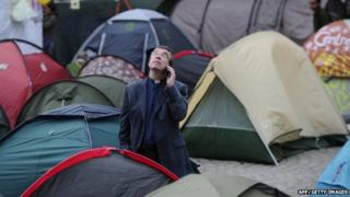 A clergyman talks on his mobile while standing among the tents outside St Paul's Cathedral in London