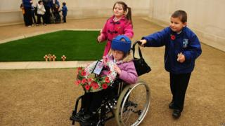 Two children push a third child in wheelchair, carrying a wreath