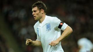 James Milner running on football pitch with black armband showing red poppy