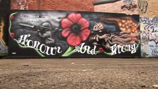 "Large painting on wall saying ""hope and glory"" with a poppy above it, next to a soldier pointing a gun."