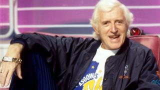 Jimmy Savile sitting in red chair