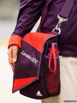 A volunteer for the London 2012 Olympics wearing their new uniform with bag and umbrella.