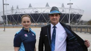 Two of the technical officials for the London Games show off their uniform in front of the Olympic Stadium.