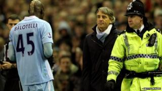 Roberto Mancini looks at Mario Balotelli as he heads for the dressing room