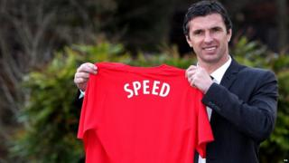 Gary Speed holds up a Wales shirt with his name on the back