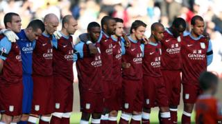 Aston Villa players stand for a moments silence in memory of Wales manger Gary Speed.
