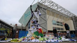 People gather around tributes outside Leeds United football ground in memory of Speed