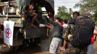 Military personnel help to evacuate a village near Iligan City, Philippines, 17 December 2011
