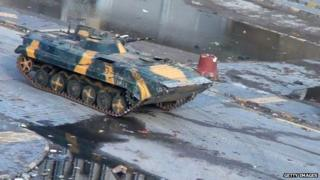 A tank drives through Homs