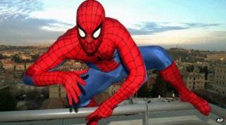 Spiderman crouching on a building